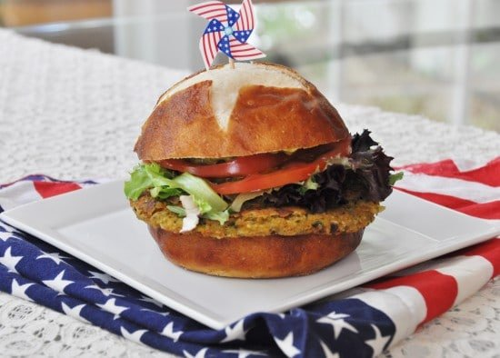 A chickpea burger with lettuce and tomato on a square white plate that's sitting on an American flag napkin.