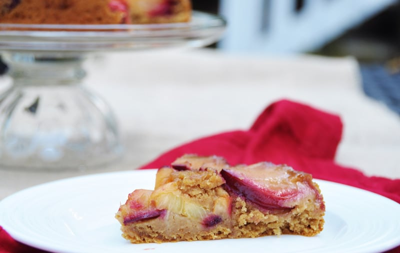 Vegan-Plum-Tart sliced on a white plate with a red napkin and the whole tart on a glass cake plate in the background
