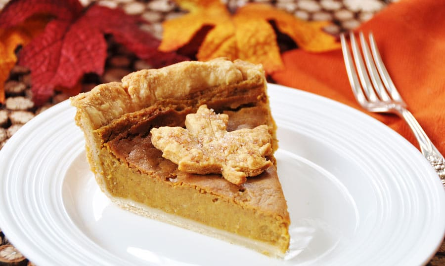 A slice of vegan pumpkin pie with a leaf made out of dough in the center, sitting on a white plate