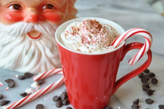 Vegan Peppermint Mocha in a red mug with whipped cream and a candy cane and a Santa cookie jar in the background