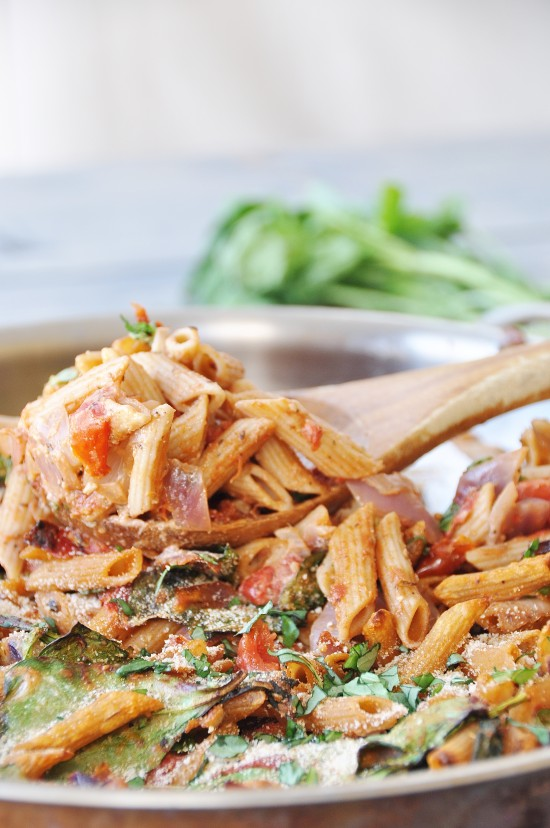 One of our top recipes Vegan Penne Pasta Casserole in a round copper pan with a wood spoon taking some out of the pan