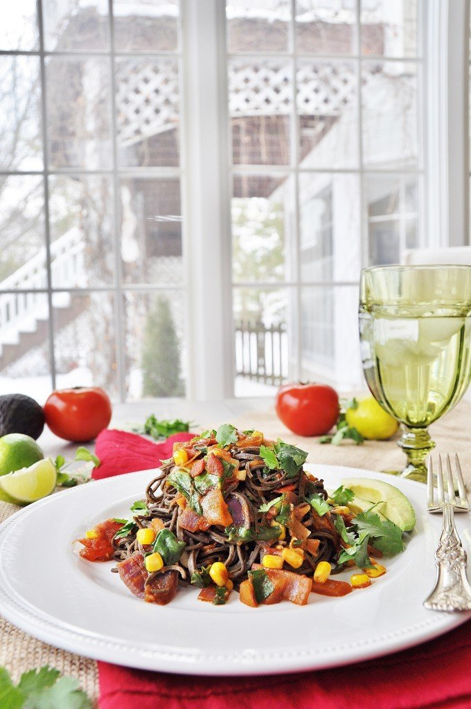 Mexican Black Bean Spaghetti on a white plate with a silver fork on the edge. A green glass with water, tomatoes, limes, and an avocado and cilantro are in the background.