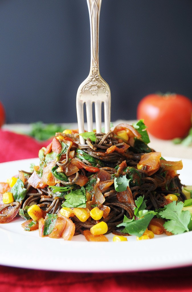 Mexican Black Bean Spaghetti with corn, onions and cilantro piled on a white plate with a silver fork sticking in the center. A red napkin is tucked under the plate and a red tomato is in the background.