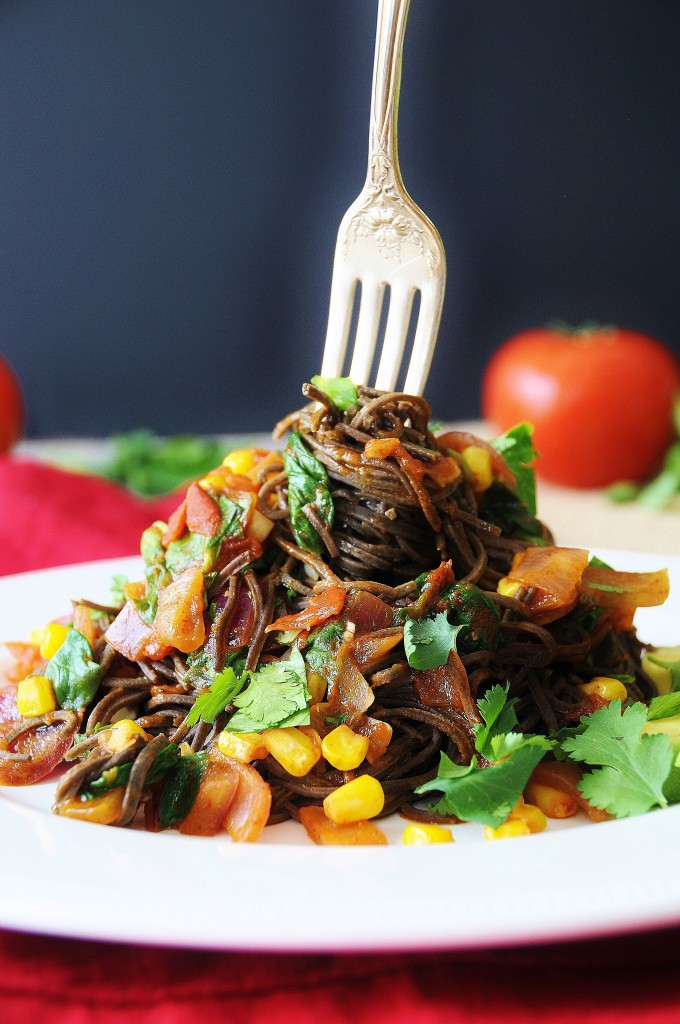 Mexican Black Bean Spaghetti piled up with a silver fork in the center wrapping the spaghetti.
