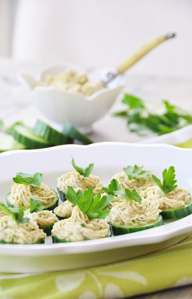 Cannellini Bean Dip on Cucumber Chips on a white platter on a green and white cloth with a white bowl of dip in the background with a yellow knife sticking out of it and cucumber chips on the table