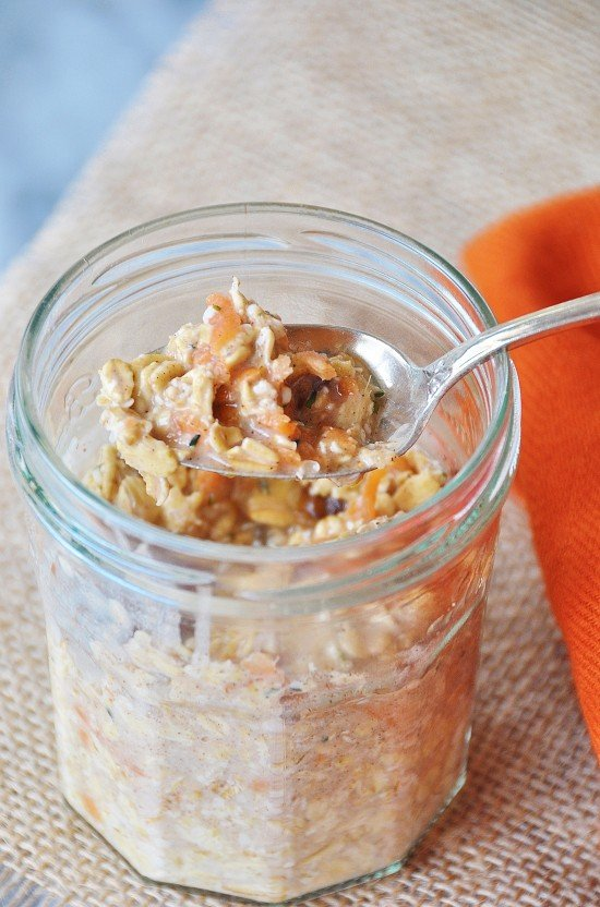 Vegan Carrot Cake Overnight Oats in a clear mason jar with a silver spoon in it and an orange napkin next to it