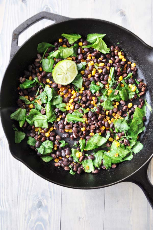 Corn-and-Bean-Hash in an iron skillet with a lime wedge and spinach leaves