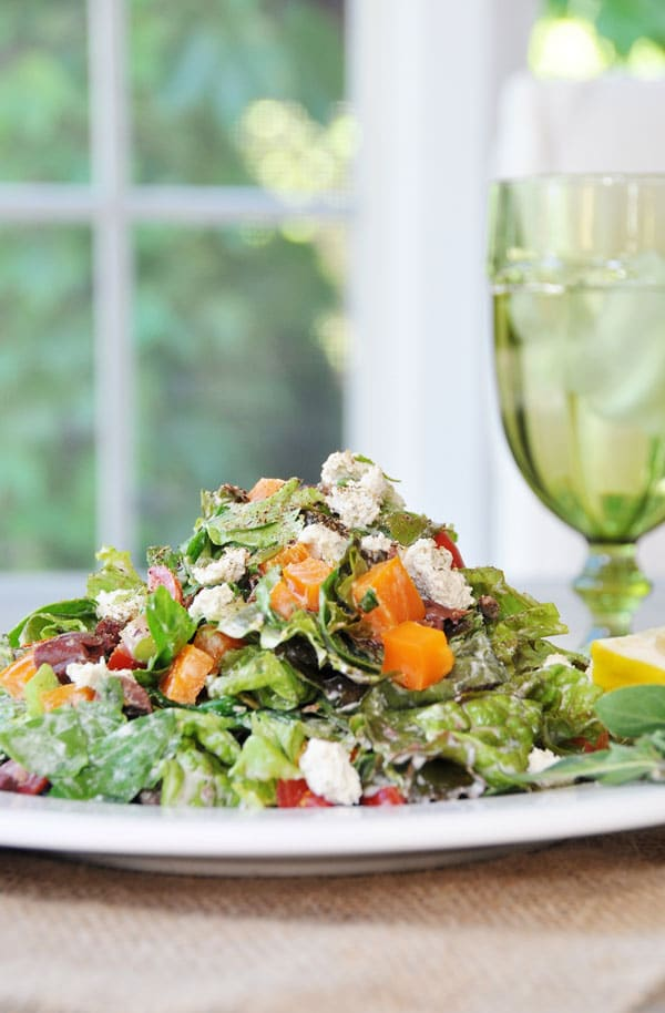 Vegetable & Herb Chopped Salad on a white plate with a green glass of water in the background