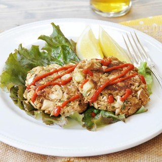 Crab cakes on a bed of lettuce with lemon on a white plate, and a beer next to the plate.
