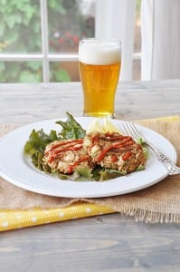 Crab cakes on a bed of lettuce on a white plate with sriracha drizzled on top with a beer in the background.