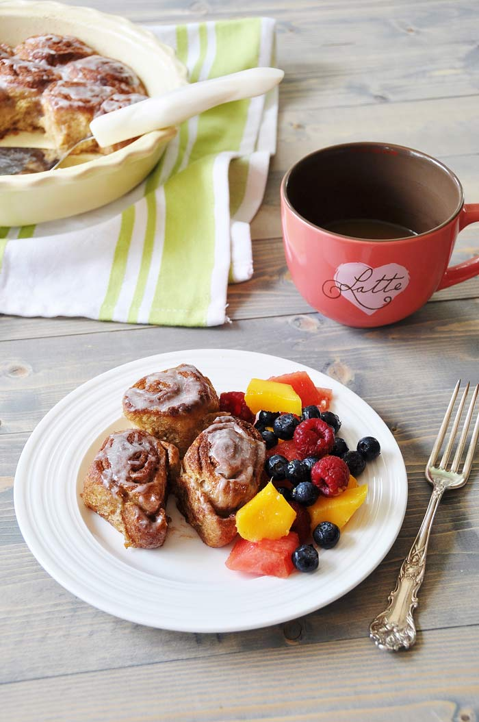 Homemade Vegan Cinnamon Rolls and fruit salad on a white plate with a pink mug of coffee and a pan of rolls next to it