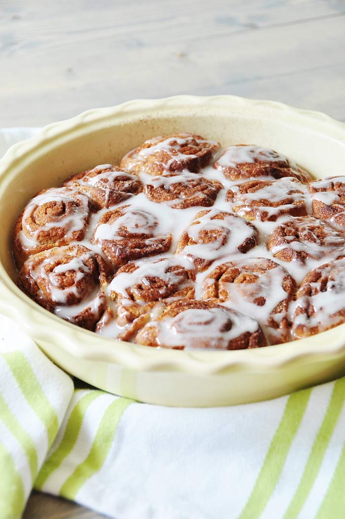 a pan of Homemade Vegan Cinnamon Rolls on a green and white striped towel