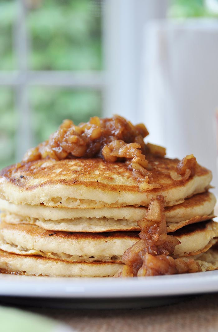 A stack of four Pancakes with Apple Spice Compote on top and dripping down the sides.