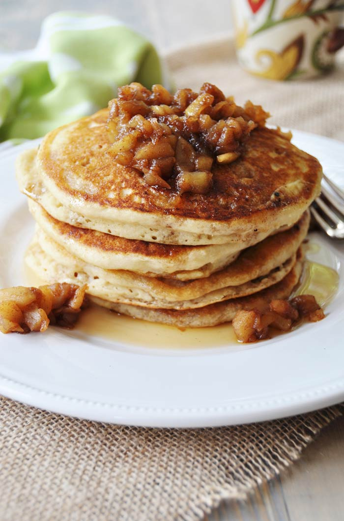 Four Old Fashioned Fluffy Vegan Pancakes with Apple Spice Compote. on a white plate with a fork on the side of the plate.