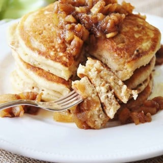 A stack of pancakes topped with syrup and chunky apples and a fork with the pancakes on it.