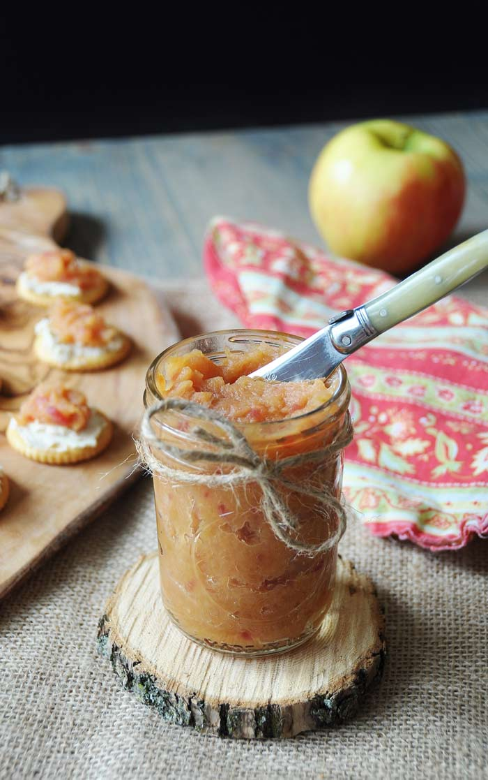 Curried Apple Relish in a glass jar with a small knife in the jar, sitting on a wood coaster with a wood tray of crackers with the relish spread on them and a red apple and red and yellow floral napkin in the background