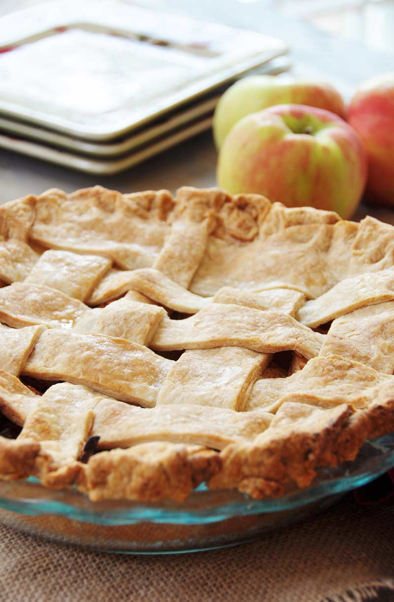 Homemade Apple Cinnamon Pie in a glass pan with a lattice top and red apples and three square plates behind it.