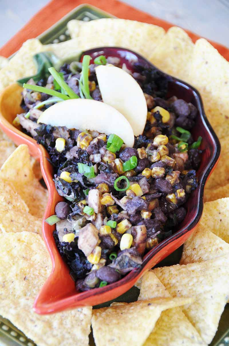 Better Beans Cuban Black Bean Dip in a red pepper shaped dish with two apple wedges and a sprig of rosemary on top and corn chips surrounding the bowl