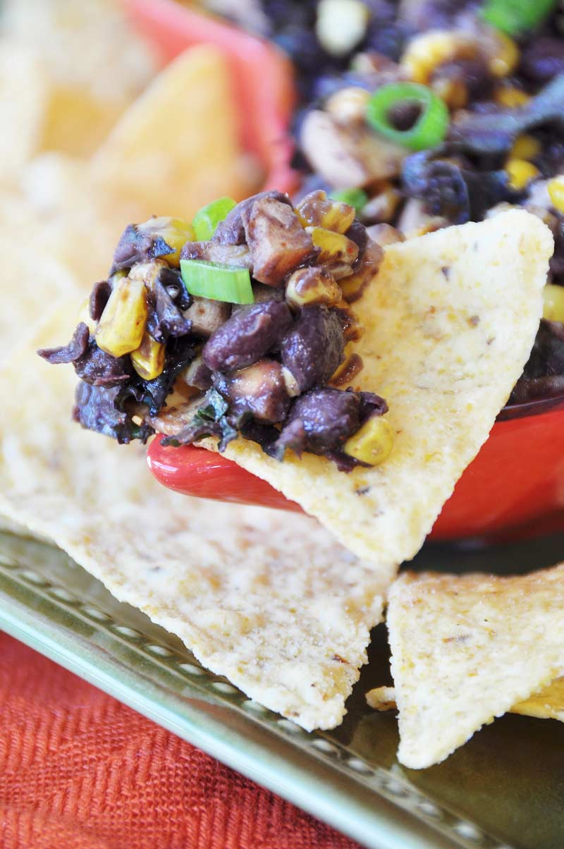 Cuban Black Bean Dip with Roasted Corn, Apples, and Kale being scooped up in a corn chip