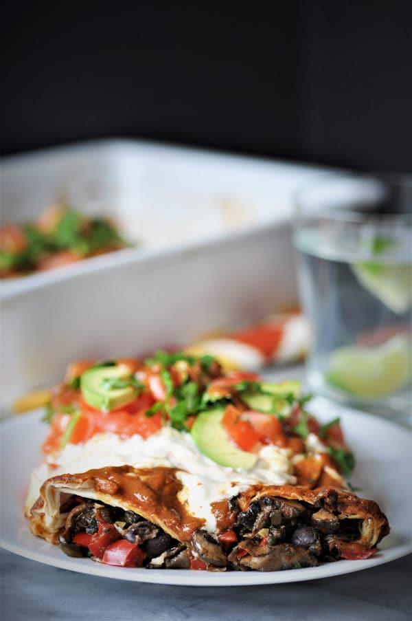 vegan black bean & mushroom enchiladas on a white plate with cashew cream sauce and sliced avocados and chopped cilantro.