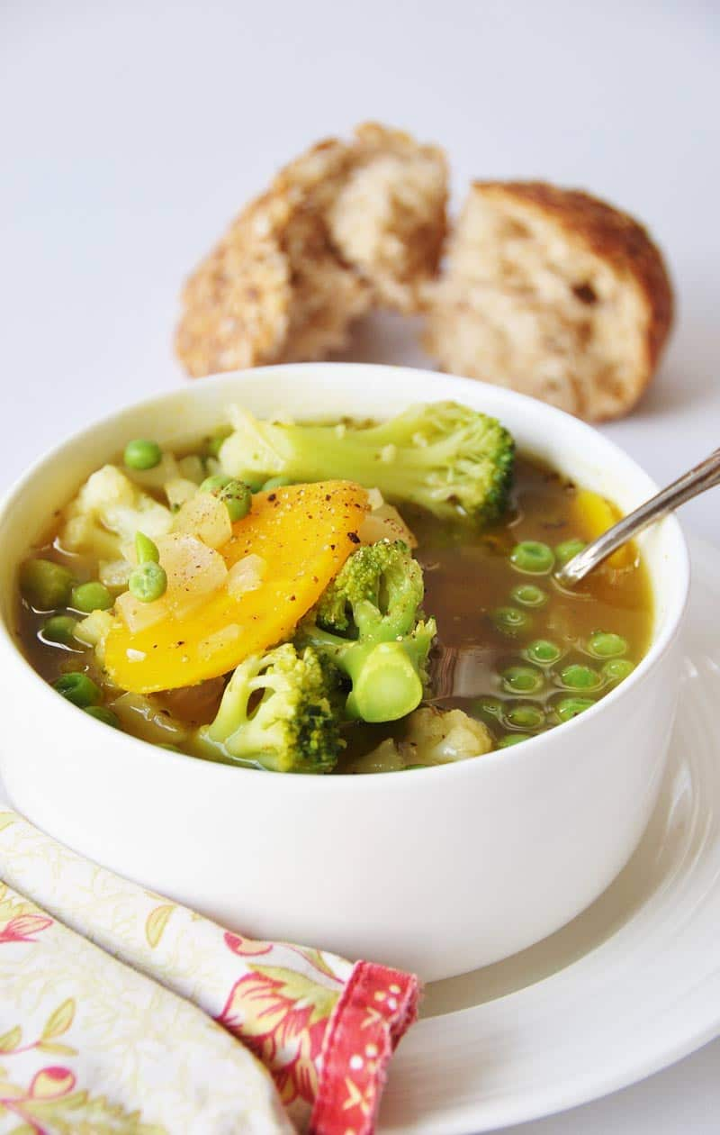 7 Ingredient 30 Minute Vegetable Soup in a white bowl on a white plate with a silver spoon sticking out of the bowl and a red and yellow floral napkin on the edge of the plate and pieces of torn bread in the background