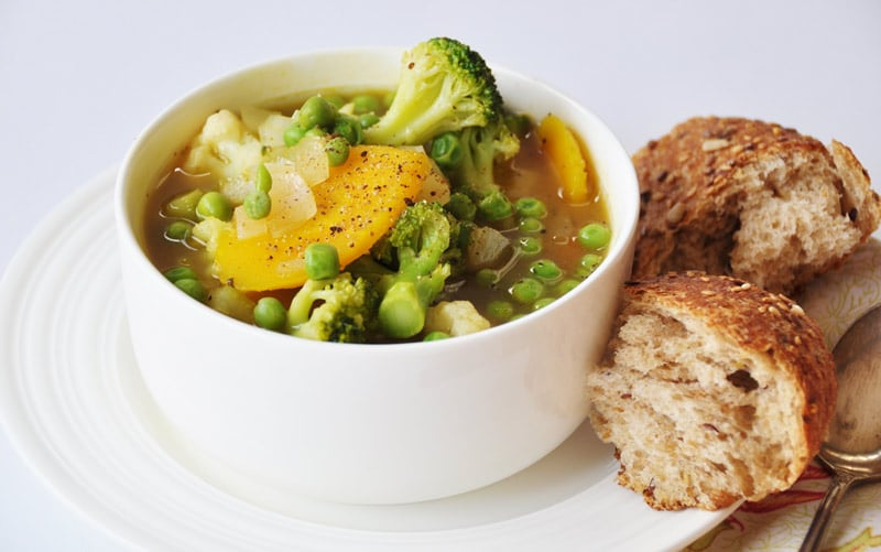 7 Ingredient 30 Minute Vegetable Soup in a white bowl on a white plate with two pieces of grain bread on the side of the plate and a silver spoon on a yellow and red floral napkin next to it.
