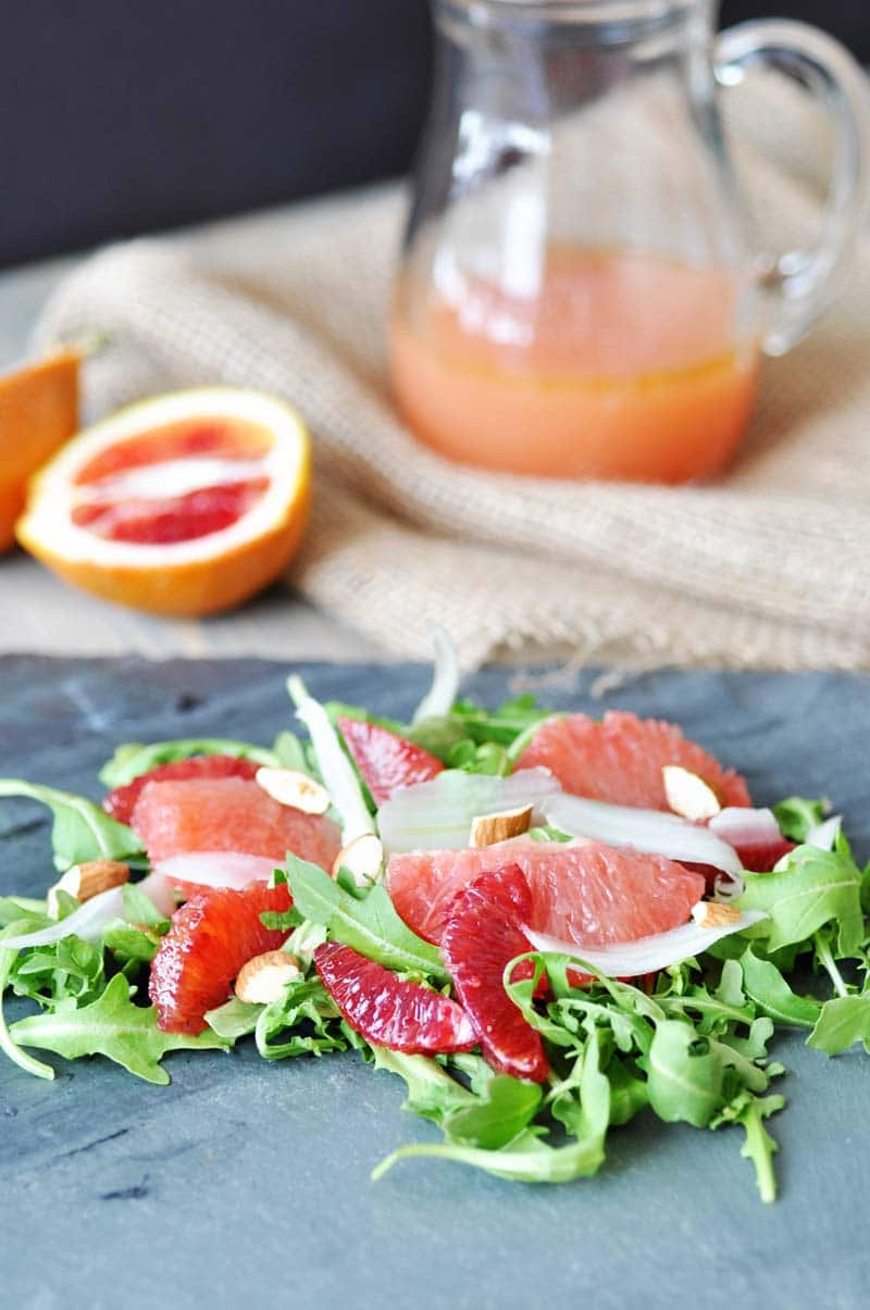 An arugula and citrus salad on a slate board with a pitcher of dressing and sliced oranges in the background.