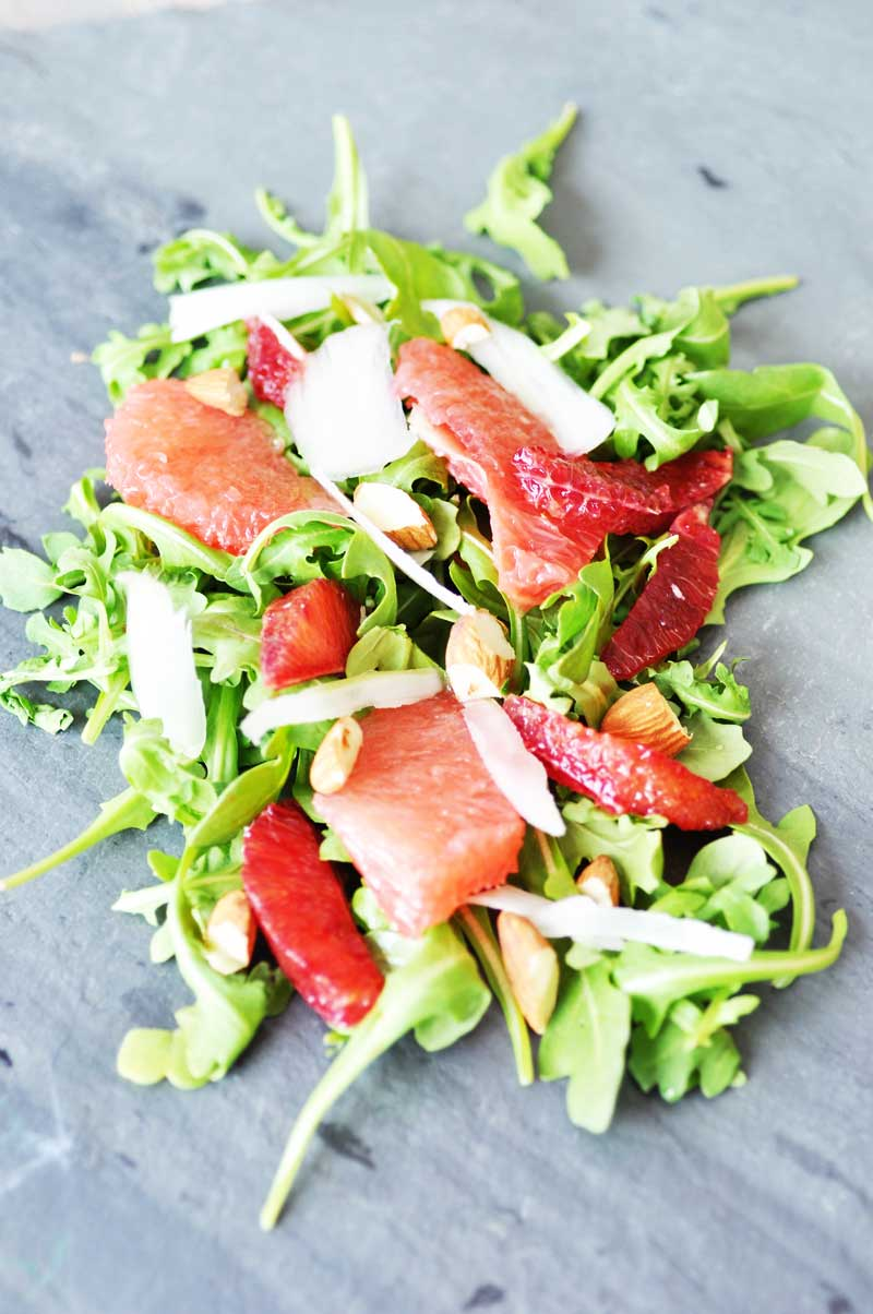An arugula and citrus salad with chopped nuts on a slate board.
