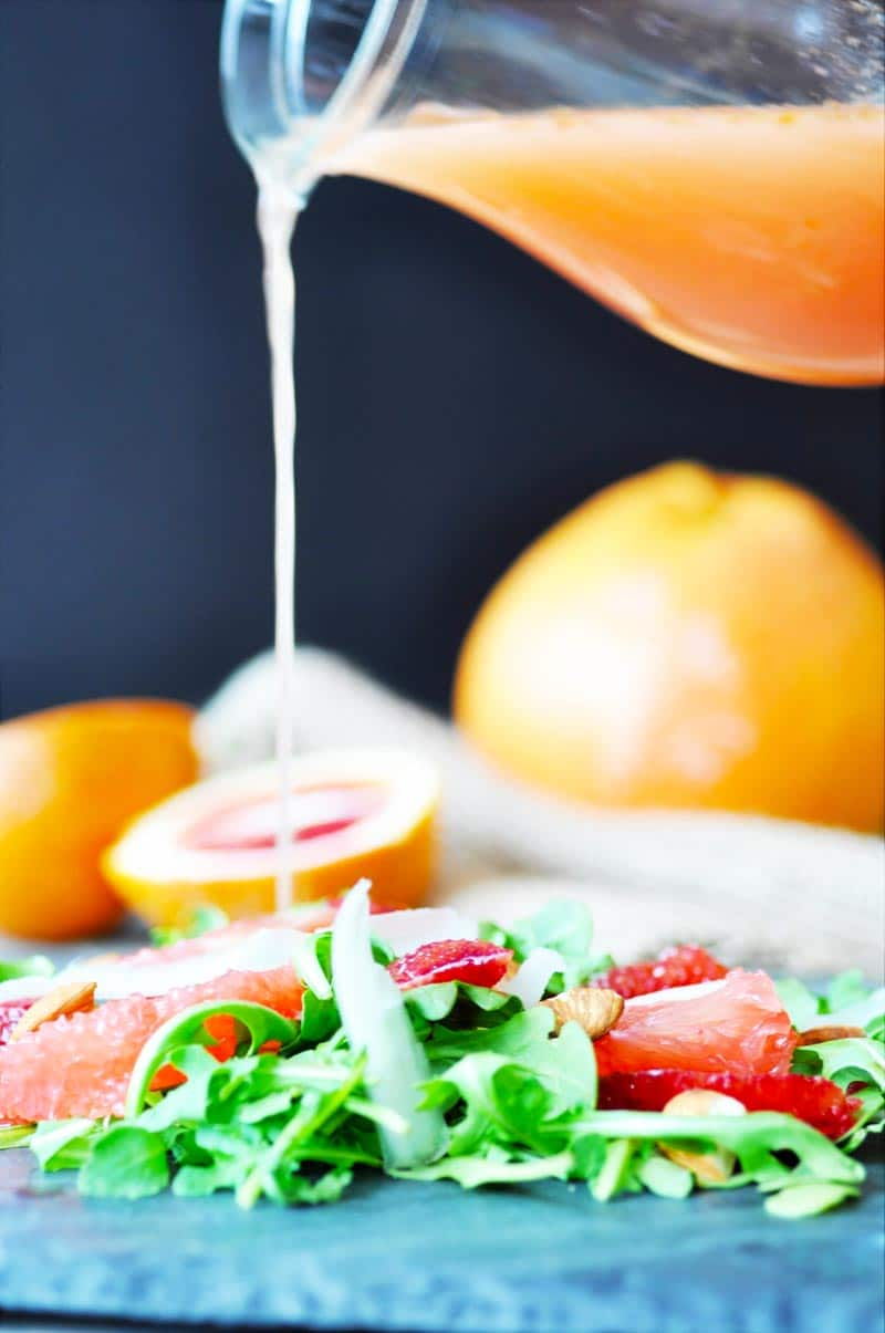 A pitcher of orange salad dressing being poured on a salad with sliced citrus and arugula.