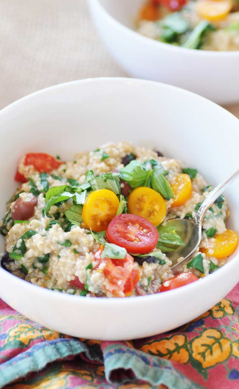 Savory vegan Mediterranean Oatmeal! This savory breakfast recipe is filled with spinach, tomatoes, Kalamata olives, basil, and steel cut oats. A delicious way to enjoy your oatmeal. This is one of my favorites! www.veganosity.com