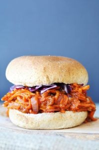 Shredded carrots with bbq sauce on a bun with red cabbage.