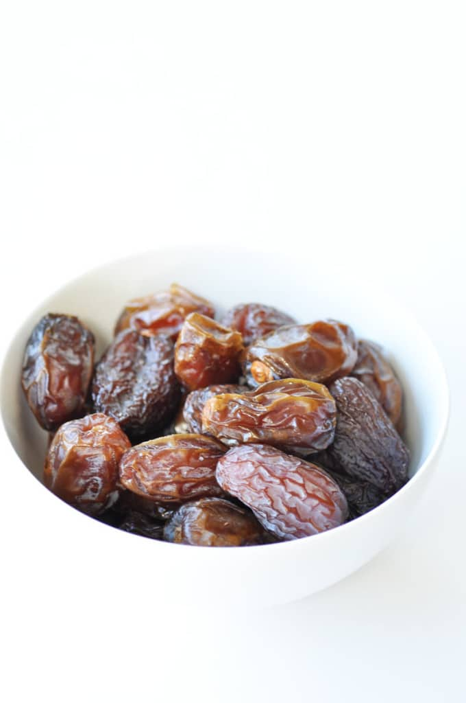 Medjool Dates in a white bowl on a white surface