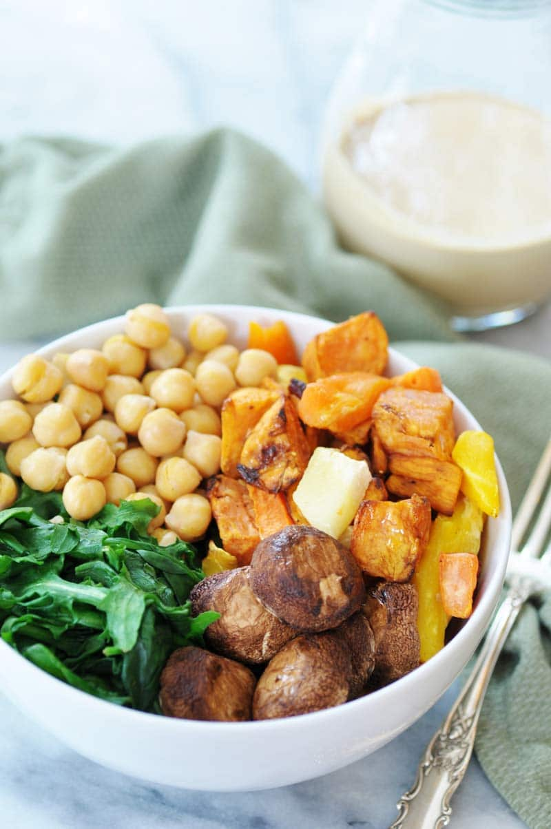 Roasted mushroom caps, sweet potatoes, garbanzo beans, and spinach in a white bowl with a silver fork, green napkin, and pitcher of tahini dressing next to it.