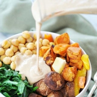A white bowl filled with roasted vegetables with a glass pitcher of dressing being poured over it