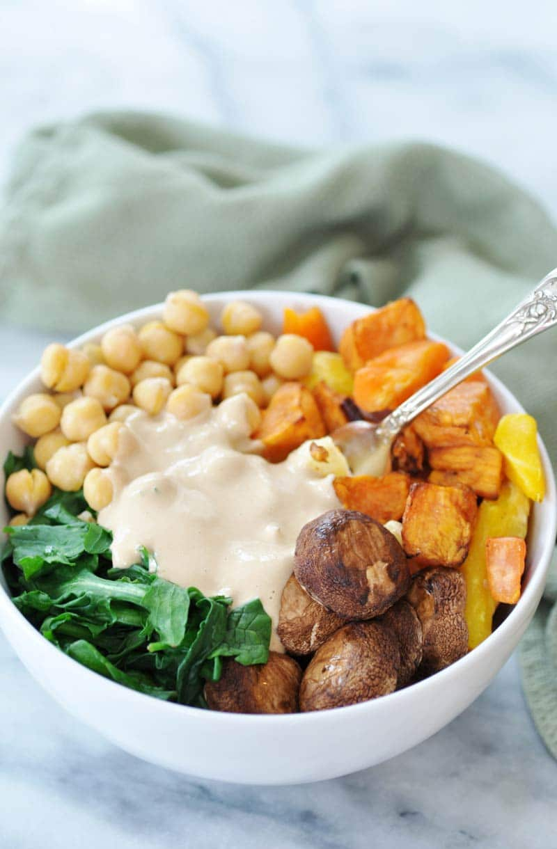 Roasted mushroom caps and sweet potatoes with spinach and chickpeas, and garlic tahini dressing in the center with a silver fork in the bowl