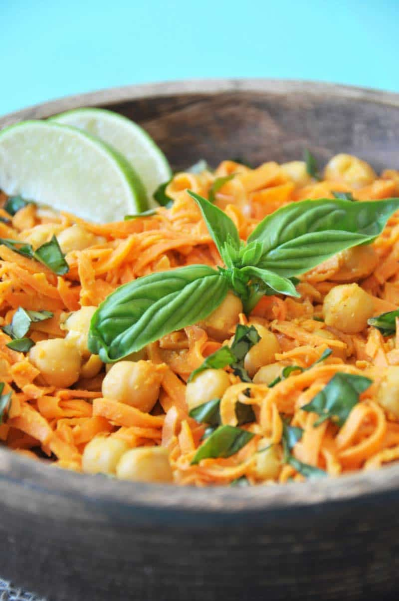 Sweet potato noodles and chickpeas with basil in a wooden bowl with 2 lime wedges garnishing the side of the bowl.