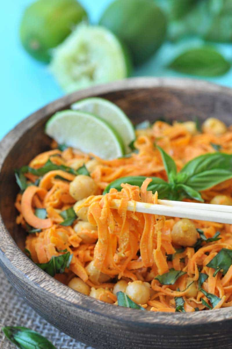 A pair of chopsticks lifting sweet potato noodles out of a wooden bowl that's filled with the noodles, chickpeas, basil, and two lime wedges.