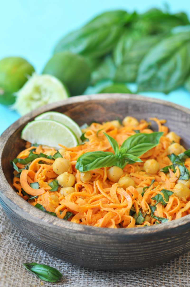 A wooden bowl with sweet potato noodles, chickpeas, and basil and lime wedges, with a pile of basil and limes in the background.