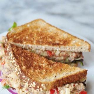 A tuna salad sandwich on toast, cut in half on a white plate.