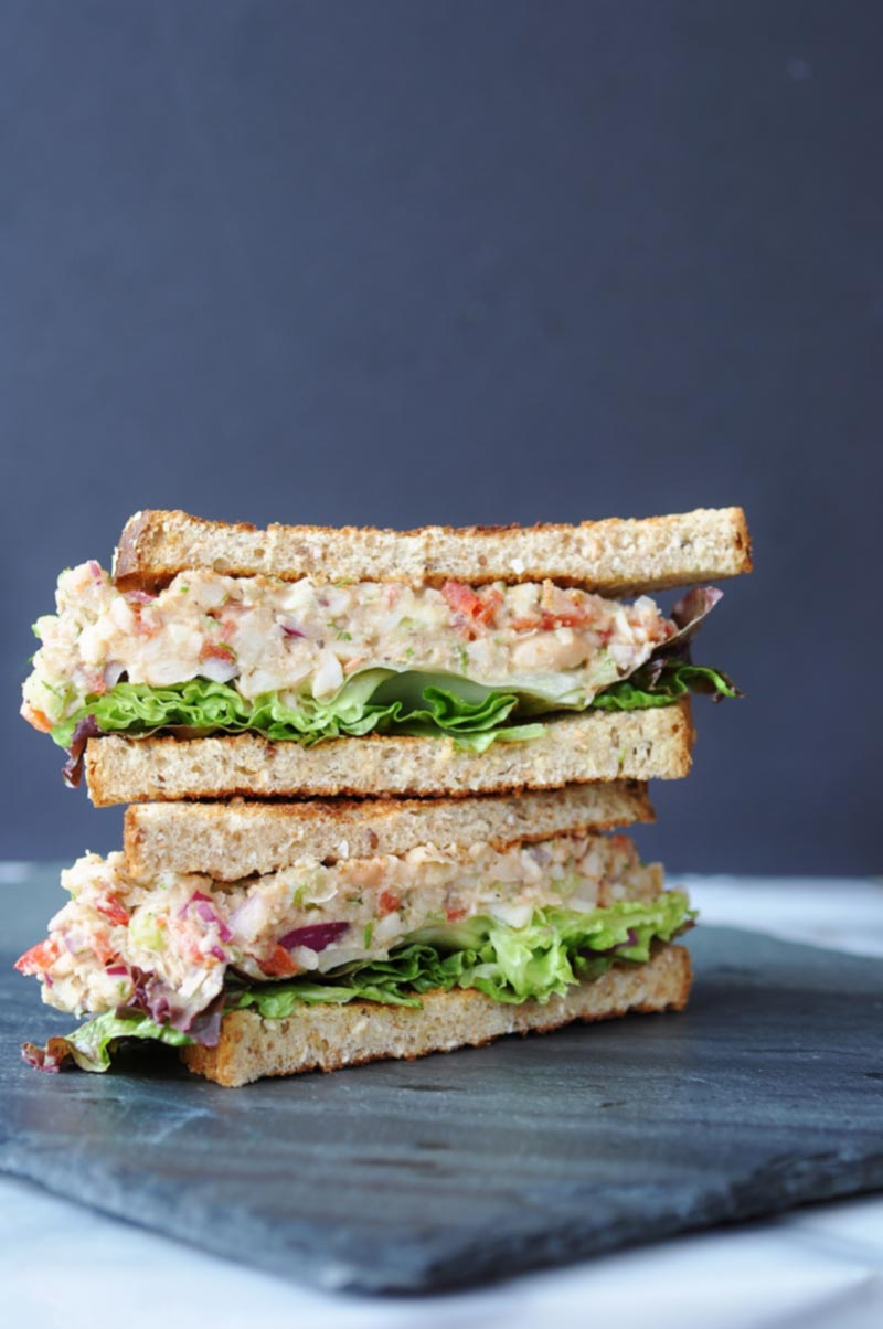 A tuna salad sandwich on toast, cut in half and stacked on a slate board.