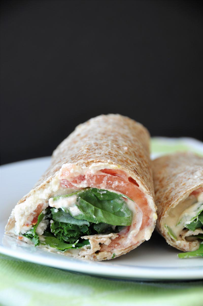 A ridiculously easy wrap stuffed with hummus, vegan ricotta cheese, kale, spinach, and tomato! Take it to work or school, or slice it into rolls for appetizers! www.veganosity.com
