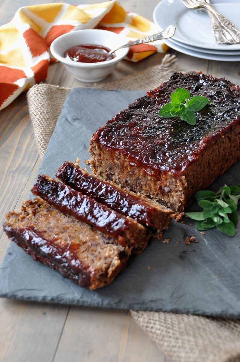 Sliced Vegan meatloaf on a slate tray with fresh herbs next to a yellow and orange napkin and a white dish of extra sauce and plates and forks