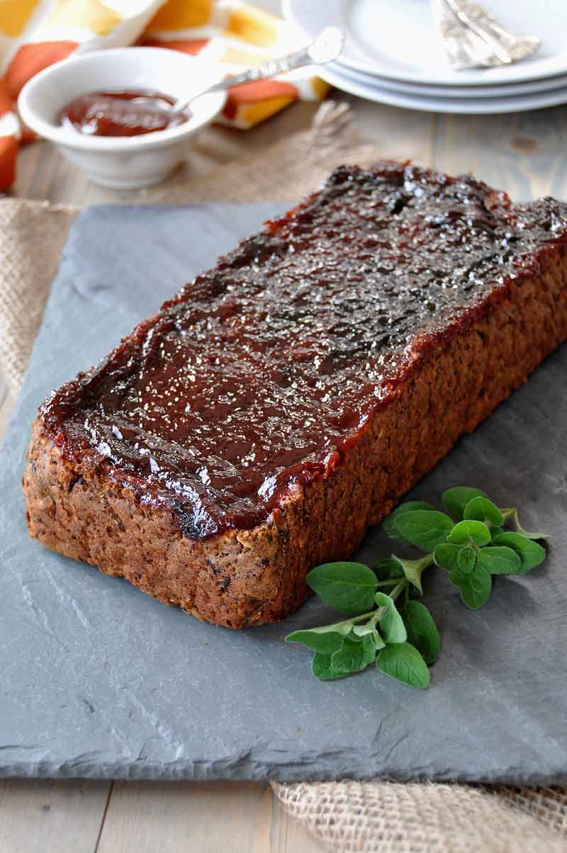 Vegan meatloaf on slate plate with a sprig of fresh oregano and a white dish of BBQ sauce and white plates and silver forks behind it.