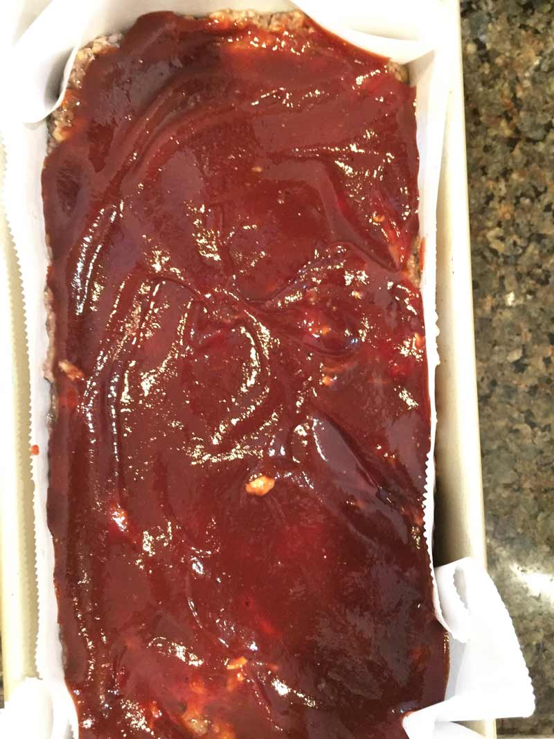 uncooked vegan meatloaf with BBQ sauce spread over the top in a bread pan with parchment paper