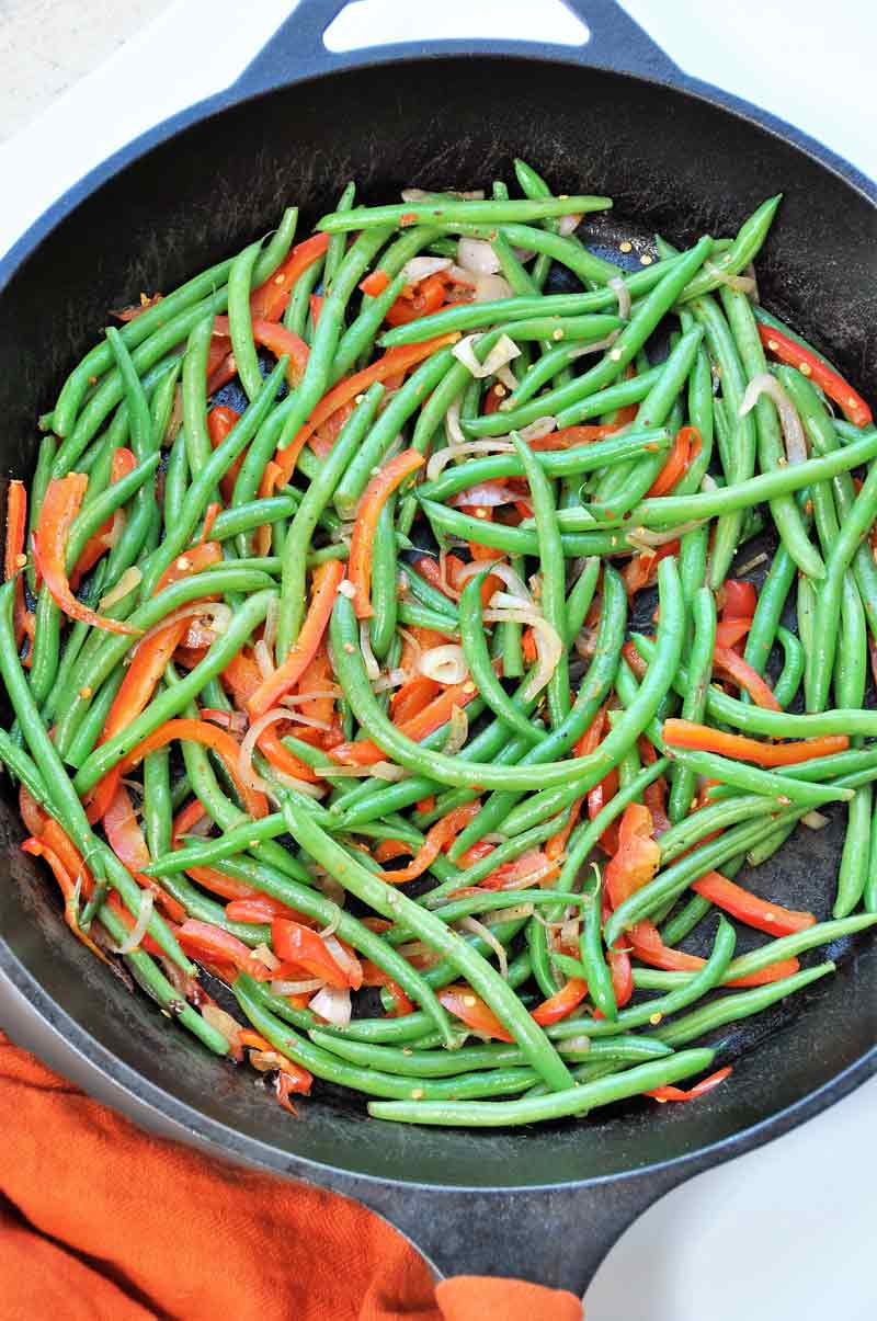 Green beans and red pepper in an iron skillet.