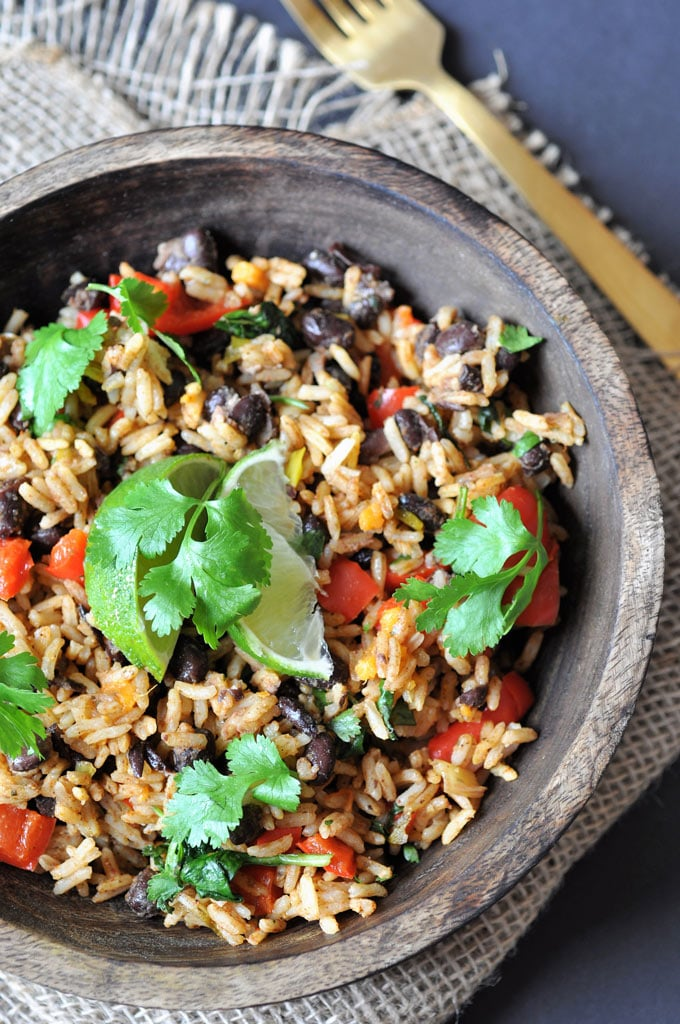 Healthy and easy vegetable black beans and rice is one of our top recipes in a wood bowl on a burlap cloth and a gold fork is on the wood table next to it