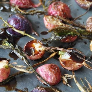 A slate board with roasted radishes and balsamic vinegar.