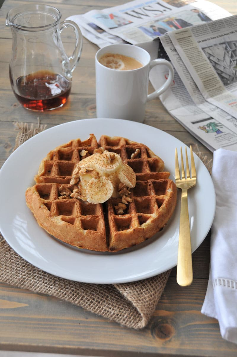 A Belgian waffle with sliced bananas and nuts on a white plate with a gold fork on the side, and a pitcher with maple syrup and a white mug of coffee in the background.