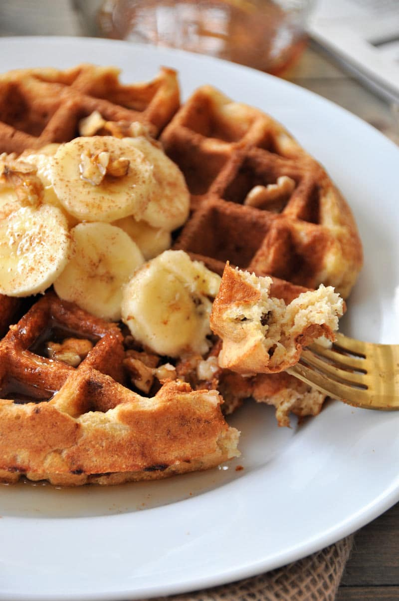 A gold fork with a piece of Belgian waffle and the rest of the whole waffle topped with banana slices and nuts on a white plate.