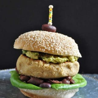 A Hummus burger on a silver plate with an olive stuck on the top with a toothpick